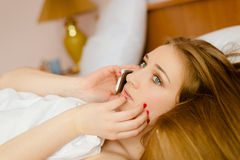 Young anxious pretty lady talking on phone lying. Close up picture of young anxious pretty lady with beautiful long hair talking on phone lying in bed Royalty Free Stock Photo