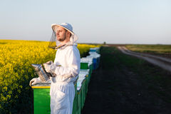 Young apiarist looking at the Sun. Young proud apiarist holding a smoker on a rapeseed field and looking into the sun. Selective focus, narrow depth of field Stock Images