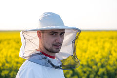 Young apiarist. On the rapeseed field. Selective focus, narrow depth of field Stock Photography