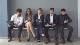 Young applicants are awaiting interview. a group of young people bored waiting for job interview. recruitment to the. Company Royalty Free Stock Photos