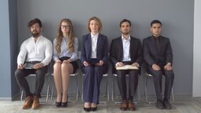 Young applicants are awaiting interview. a group of young people bored waiting for job interview. recruitment to the. Company Royalty Free Stock Images
