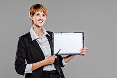 Young apprentice holding a clipboard and pointing with a pen Royalty Free Stock Photography