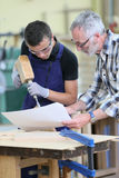 Young apprentice with instructor working on wood royalty free stock photos