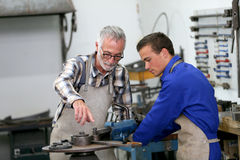 Young apprentice in ironworks with monitor stock photography