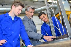 Young apprentice with professional metallurgist stock photography