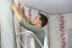 Young apprentice putting wallpaper royalty free stock photography
