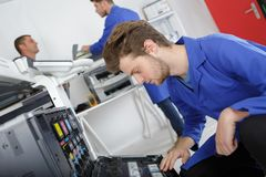 Young apprentice with screwdriver in hand fixing printer royalty free stock photo