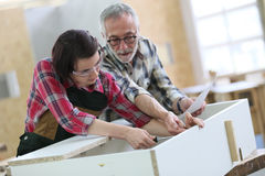 Young apprentice with senior craftsman of carpentry. Young women with senior craftsman in carpentry class stock photo