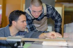 Young apprentice with teacher working on piece wood. Young apprentice with teacher working on piece of wood royalty free stock photography