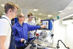 Young apprentices in technical vocational training are taught by. Older trainers on a cnc lathes machine Stock Images