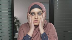 A young Arab girl in red hijab is surprised, shows an emotion of surprise. Looks at the camera, portrait. 60 fps
