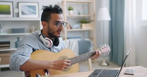Young Arab guitarist playing the guitar and using laptop at home alone. Young Arab guitarist is playing the guitar and using laptop typing at home alone enjoying stock video