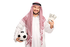 Young Arab holding a football and money Royalty Free Stock Images