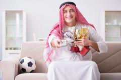 The young arab man watching football sitting on sofa Stock Photos