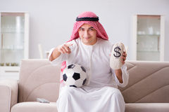 The young arab man watching football sitting on sofa Stock Image