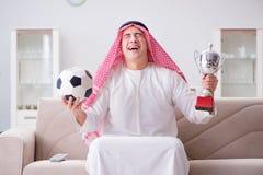 The young arab man watching football sitting on sofa Royalty Free Stock Photos
