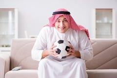 The young arab man watching football sitting on sofa Stock Photo