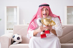 The young arab man watching football sitting on sofa Royalty Free Stock Photo