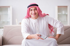 The young arab man watching tv sitting on the sofa Royalty Free Stock Photo