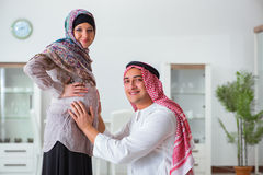 The young arab muslim family with pregnant wife expecting baby Stock Photos