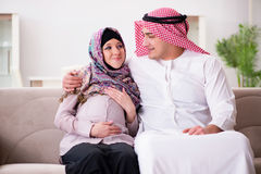The young arab muslim family with pregnant wife expecting baby Stock Image