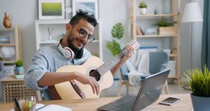 Young Arab playing the guitar and using laptop at table in apartment. Young bearded Arab in glasses is playing the guitar and using laptop at table in light stock video footage