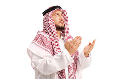 Young Arab praying to god and looking up. Young Arab with a red checkered veil praying to god and looking up isolated on white background Royalty Free Stock Photos