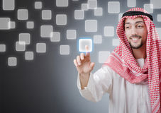 Young arab pressing virtual buttons. On grey stock photography
