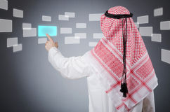 Young arab pressing virtual buttons. On grey royalty free stock image