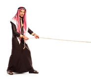 Young Arab pulling a rope isolated on white Stock Photo