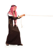 Young Arab pulling a rope isolated on white Stock Photography