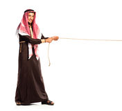 Young Arab pulling a rope isolated on white Stock Photos