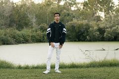 Young Arab Teen Model Posing in Nature at the Park. Attractive Middle Eastern Male Model Posing and Smiling for the Camera Outside Stock Photography
