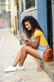 Young Arab woman looking at her digital tablet outdoors. royalty free stock photography