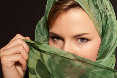 Young arab woman with veil showing her eyes dark. Young arab woman with veil showing her eyes on dark gray background stock photography