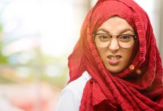 Young arabian woman wearing hijab isolated over natural background. Young arab woman wearing hijab angry and stressful frowns face in dissatisfaction, irritated Stock Photography