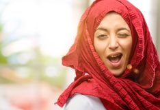 Young arabian woman wearing hijab isolated over natural background. Young arab woman wearing hijab blinking eyes with happy gesture Stock Photo