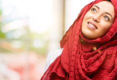 Young arabian woman wearing hijab isolated over natural background. Young arab woman wearing hijab confident and happy with a big natural smile laughing looking Royalty Free Stock Photo