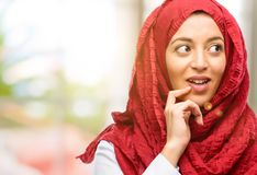 Young arabian woman wearing hijab isolated over natural background. Young arab woman wearing hijab confident and happy with a big natural smile laughing Stock Photos