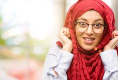 Young arabian woman wearing hijab isolated over natural background. Young arab woman wearing hijab covering ears ignoring annoying loud noise, plugs ears to Royalty Free Stock Photo
