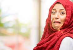 Young arabian woman wearing hijab isolated over natural background. Young arab woman wearing hijab feeling disgusted with tongue out Stock Image