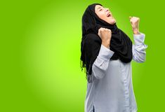 Young arab woman wearing hijab isolated over green background. Young arab woman wearing hijab happy and excited expressing winning gesture. Successful and Stock Images