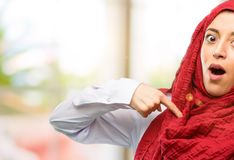 Young arabian woman wearing hijab  over natural background. Young arab woman wearing hijab happy and surprised cheering expressing wow gesture, pointing with Royalty Free Stock Image