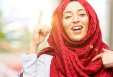 Young arabian woman wearing hijab isolated over natural background. Young arab woman wearing hijab happy and surprised cheering expressing wow gesture pointing Stock Photos