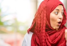 Young arabian woman wearing hijab isolated over natural background. Young arab woman wearing hijab happy and surprised cheering expressing wow gesture pointing Stock Photography
