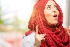 Young arabian woman wearing hijab  over natural background. Young arab woman wearing hijab happy and surprised cheering expressing wow gesture pointing up Royalty Free Stock Photos