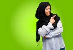 Young arab woman wearing hijab isolated over green background. Young arab woman wearing hijab pointing away side with finger Royalty Free Stock Images