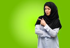 Young arab woman wearing hijab isolated over green background. Young arab woman wearing hijab pointing away side with finger Stock Images