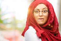 Young arabian woman wearing hijab isolated over natural background. Young arab woman wearing hijab nervous and scared biting lips looking camera with impatient Royalty Free Stock Image