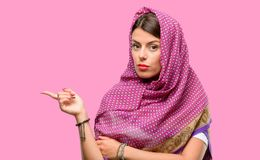 Young arab woman. Wearing hijab pointing away side with finger Royalty Free Stock Photos